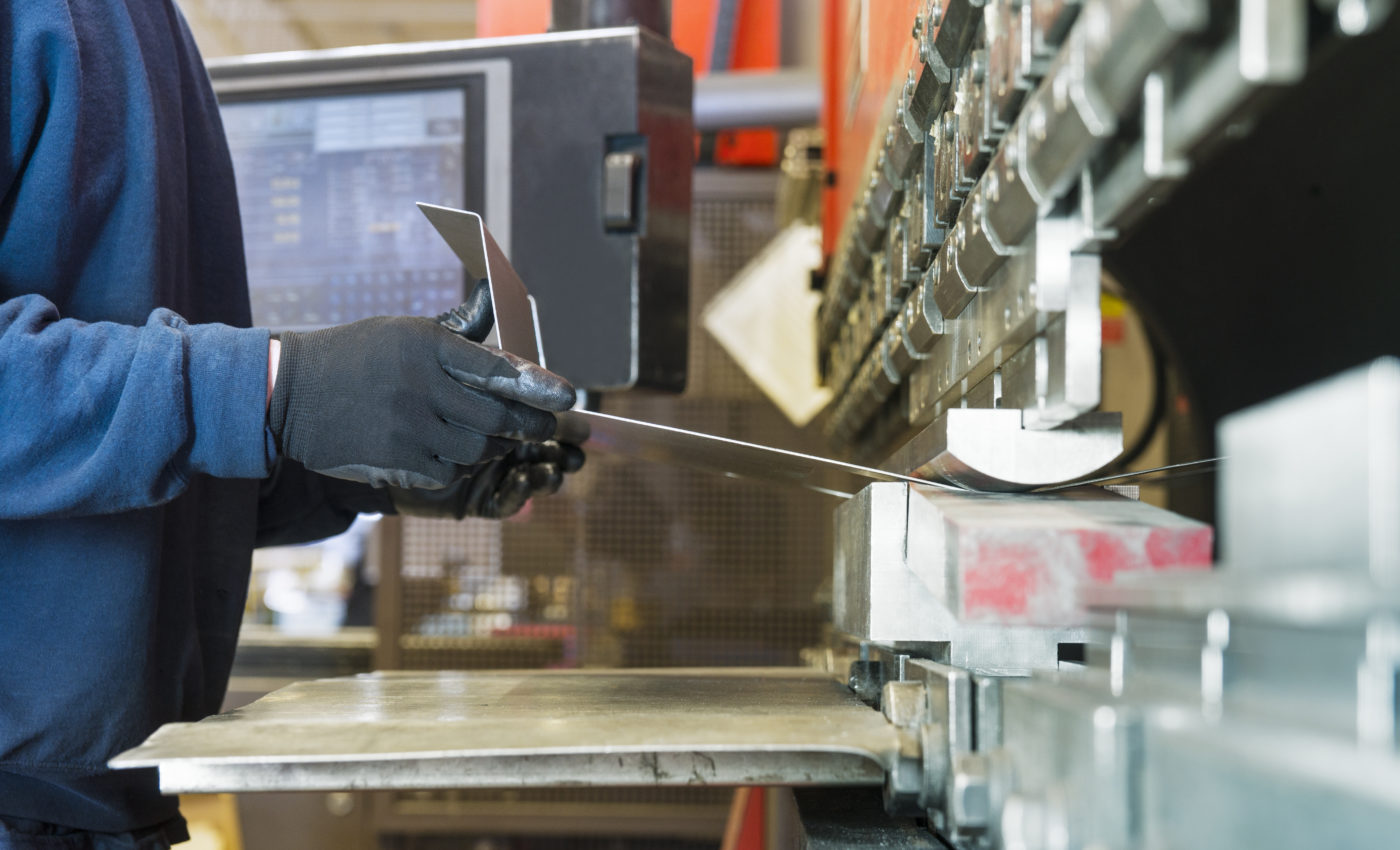 Brake press operator at work in a metal factory